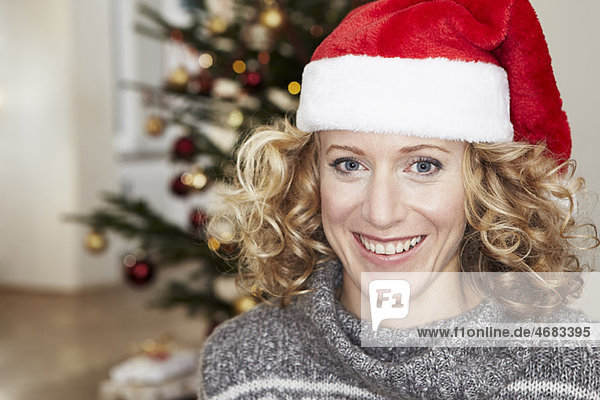 Frau vor dem Weihnachtsbaum mit Hut Frau vor dem Weihnachtsbaum mit Hut