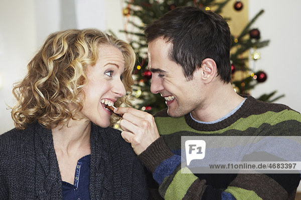 Mann füttert Frau mit Plätzchen