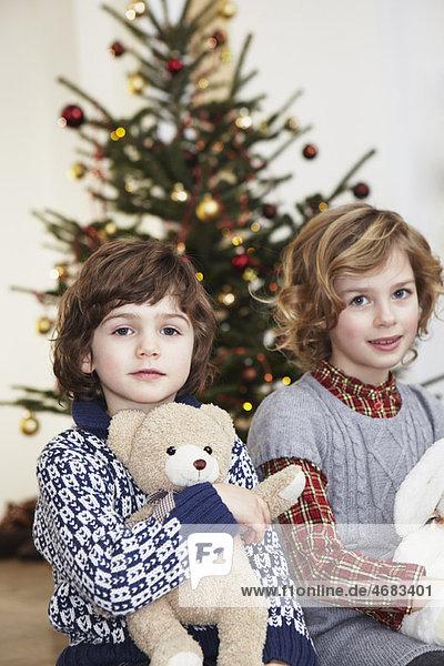 Kinder mit Kuscheltieren vor dem Baum Kinder mit Kuscheltieren vor dem Baum