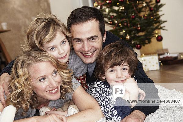 Familie auf Teppich vor dem Baum liegend Familie auf Teppich vor dem Baum liegend