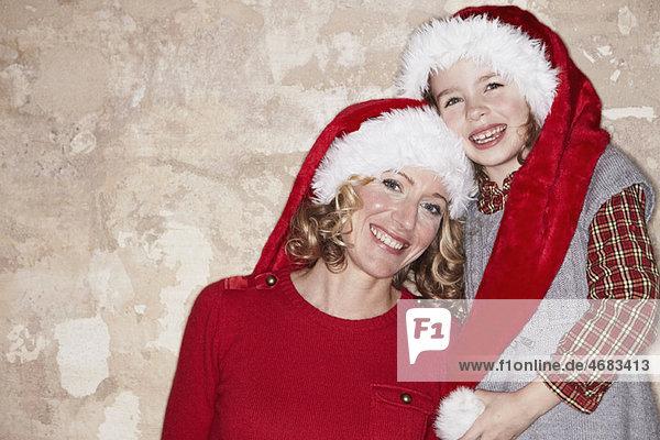 Mutter und Tochter mit Weihnachtsmützen Mutter und Tochter mit Weihnachtsmützen