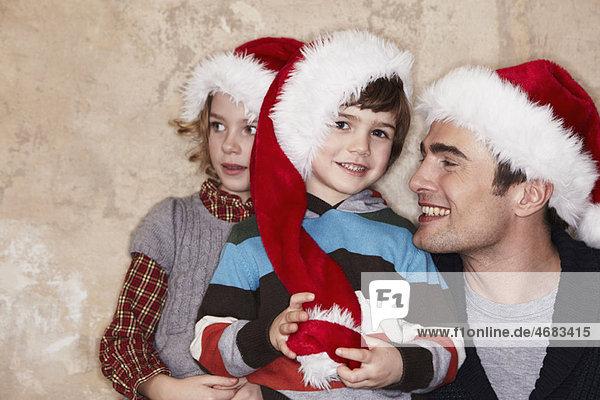 Vater und Kinder mit Weihnachtsmützen Vater und Kinder mit Weihnachtsmützen