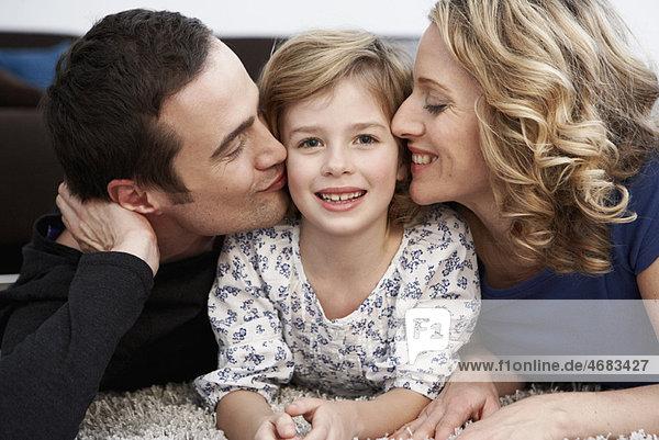 Eltern küssen Tochter auf Wangen