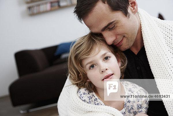 Vater und Tochter kuscheln unter dem Mantel Vater und Tochter kuscheln unter dem Mantel