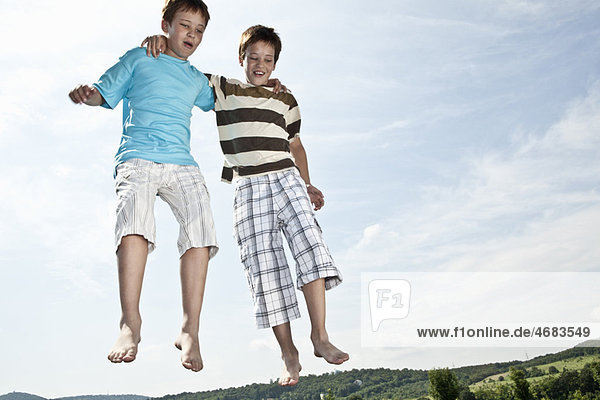 Two boys jumping on trampoline