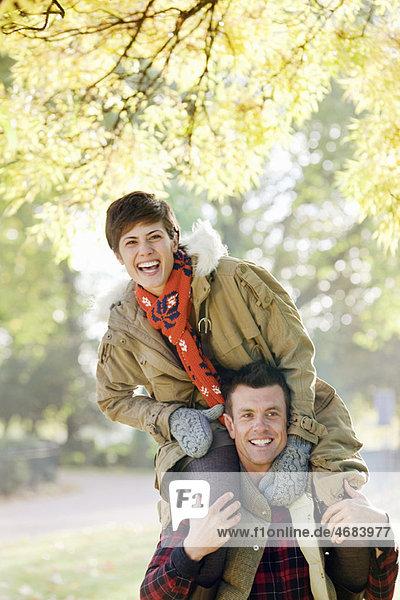 Frau auf den Schultern des Mannes im Park