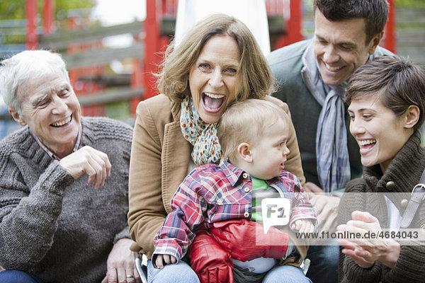 Familie mit Kind lacht im Park