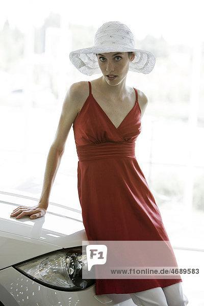 Junge Frau in rotem Kleid an einem Auto