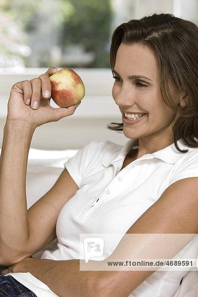 Lächelnde Frau hält einen Apfel