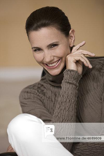 Lächelnde Frau trägt braunen Pullover