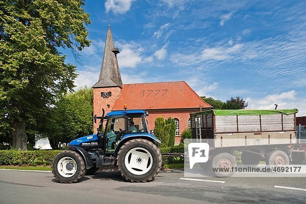 The historic brick church of Staffhorst and a blue tractor  Lower Saxony  Germany  Europe