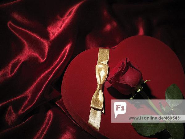 Rote  herzförmige Geschenkschachtel mit goldener Schleife und roter Rose