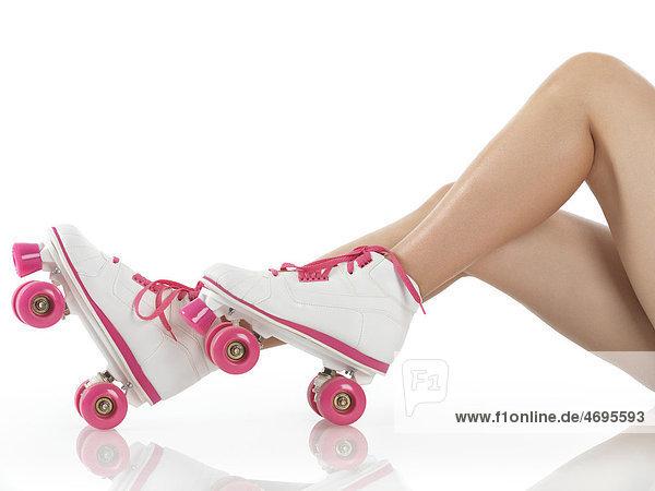 Beine einer jungen Frau mit weiß-rosa Rollschuhen  klassische Roller Girl Derby Skates  Nahaufnahme