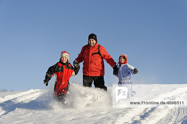 Children with their father in the snow
