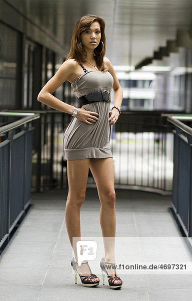 Junge Frau in kurzem grauem Kleid und hochhackigen Schuhen posiert