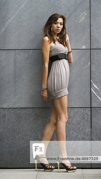 Junge Frau in kurzem grauem Kleid und hochhackigen Schuhen posiert vor Wand