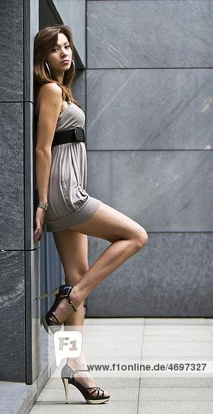 Junge Frau in kurzem grauem Kleid und hochhackigen Schuhen lehnt an Wand
