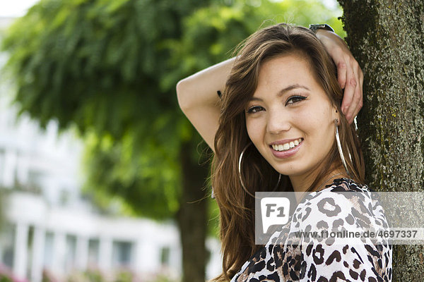 Young woman wearing leopard-print top leaning against tree