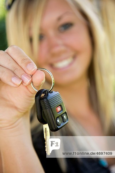 Teenage girl holding out the keys to her car