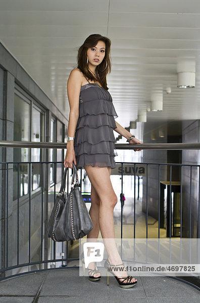 Junge Frau in kurzem grauem Kleid und hochhackigen Schuhen posiert stehend mit Tasche