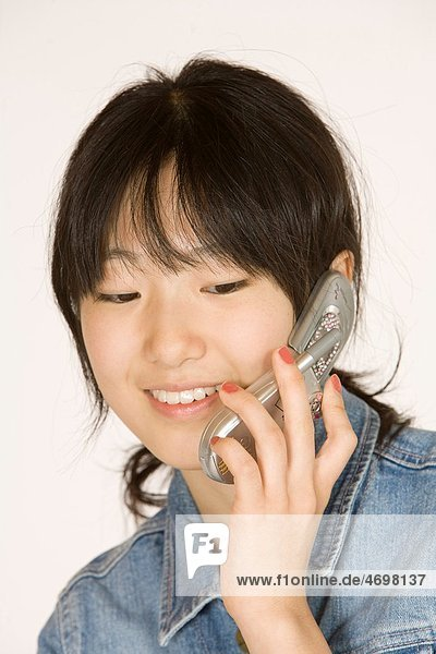 Portrait of a beautiful Asian teenager talking on a cell phone on a white background