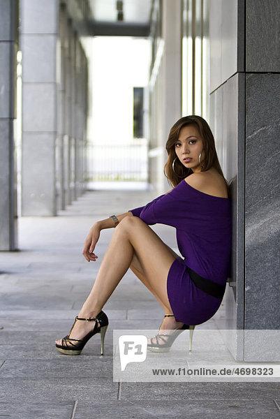 Junge Frau in kurzem lila Kleid und hochhackigen Schuhen posiert hockend an grauer Wand