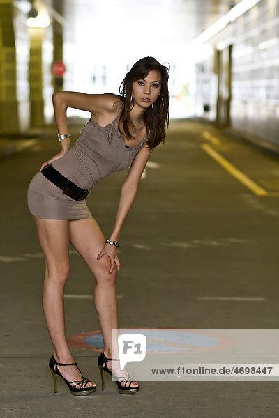 Junge Frau in kurzem beigem Kleid und hochhackigen Schuhen posiert stehend