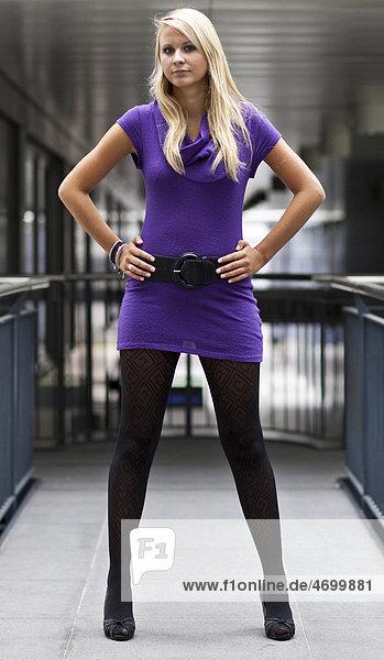 Junge blonde Frau im violetten Kleid und in hochhackigen Schuhen posiert stehend