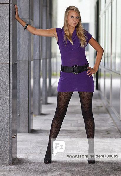 Junge blonde Frau im violetten Kleid und mit hochhackigen Schuhen posiert stehend
