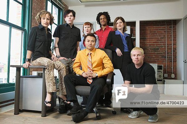 A group of seven young colleagues in an office.