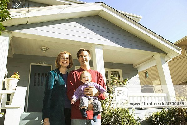 A family of three standing outside their house.