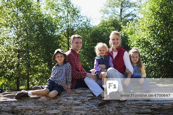 Portrait of a family of five sitting on a log.