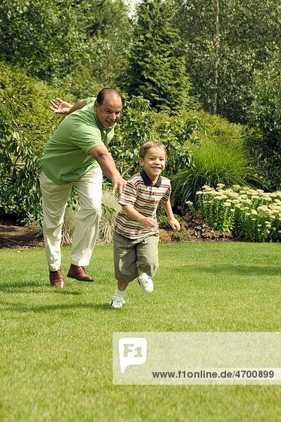 Grandfather playing with his young grandson at the park.