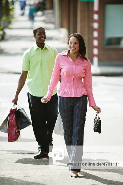 Young couple strolling and carrying shopping bags.
