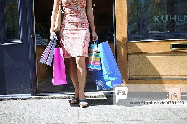 A woman emerging from a store with shopping bags.