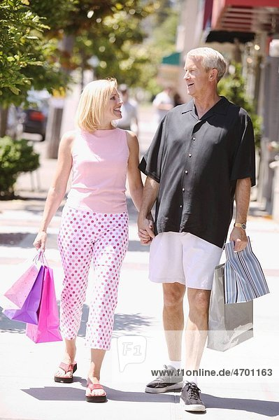 A strolling couple carrying shopping bags.