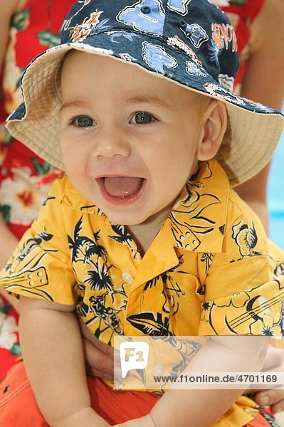 A baby boy in bright clothes and hat.