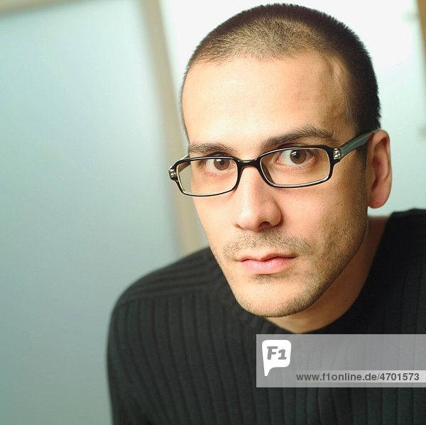 A young man wearing glasses