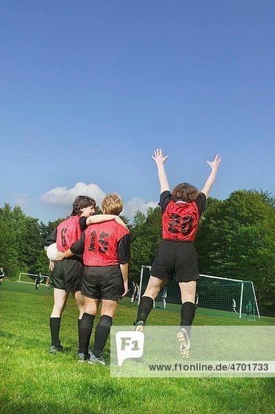 Three female soccer players celebrate a win