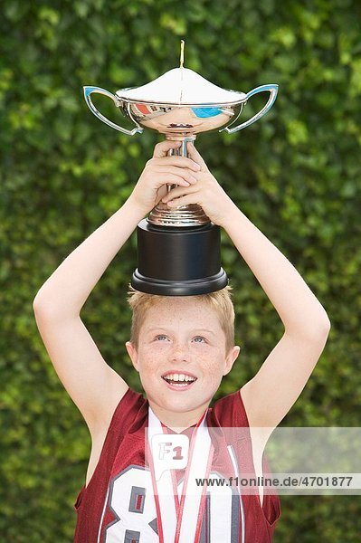 Boy balancing a trophy on his head