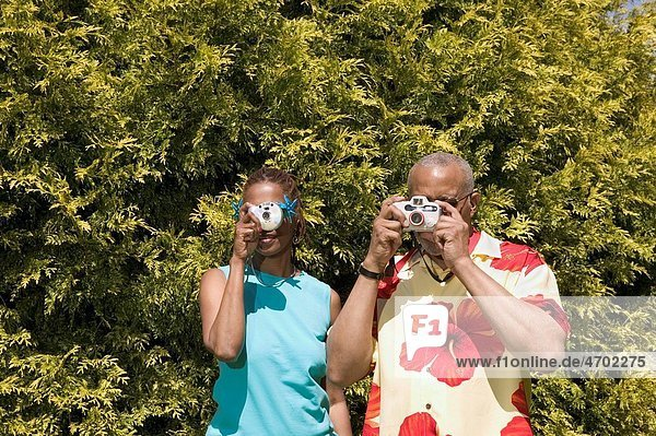 Couple with cameras taking pictures