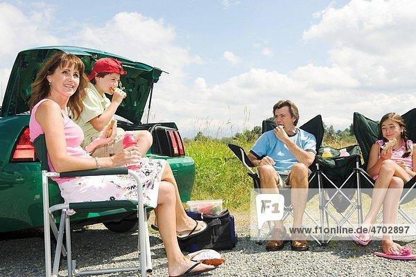 Family having picnic lunch outside car