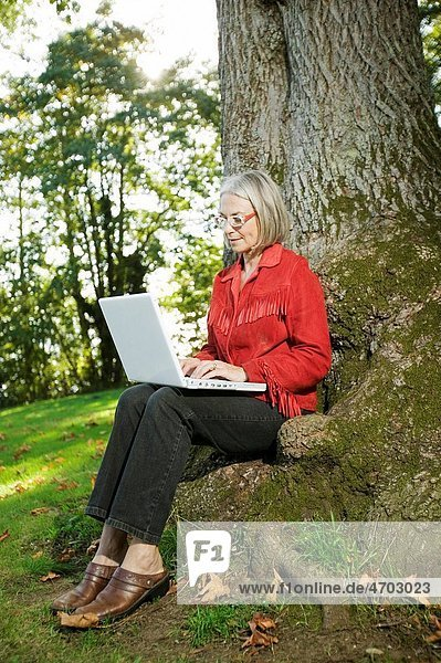 Woman with tree using laptop