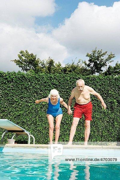 Senior couple preparing to dive into pool
