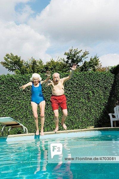 Senior couple jumping into pool