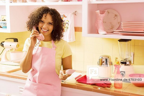 Woman talking on phone in kitchen