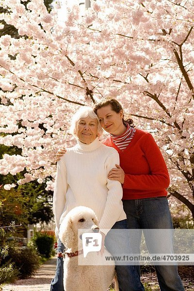 Portrait of woman with grown daughter and dog