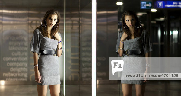 Junge Frau mit langen dunklen Haaren posiert vor Glaswand  Spiegelbild