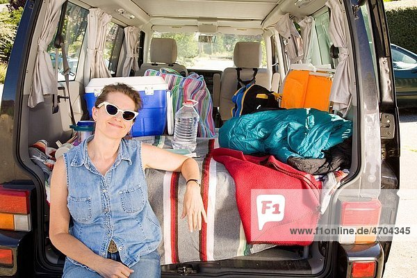 Woman sitting in trunk of car with camping gear