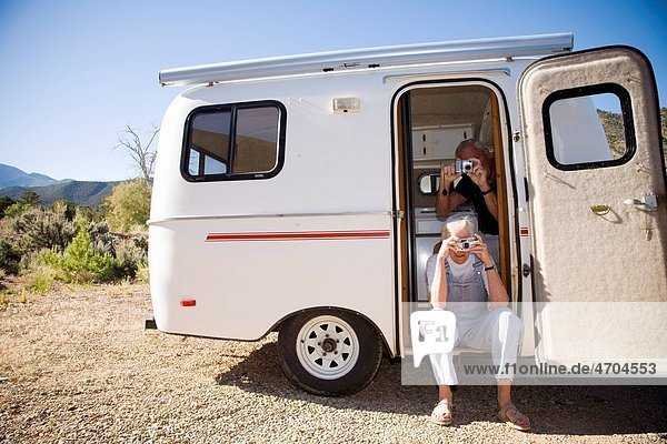 Couple taking pictures from their trailer